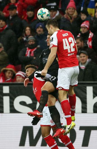 Die Mainzer Jean-Philippe Gbamin (links) und Alexander Hack (rechts) und Stuttgarts Mario Gomez kämpfen um den Ball. Foto: dpa